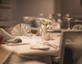 Restaurant tables are presented neatly with flowers, cutlery, glasses and napkins.