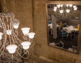 A view of a chandelier and mirror from the upstairs area of the restaurant.