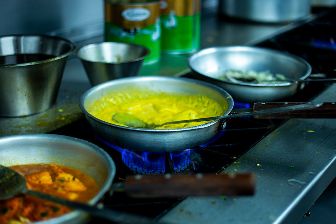 Three curry dishes being prepared in a kitchen.