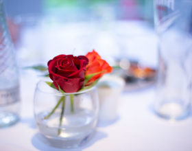 Two roses in a glass in the middle of a table.