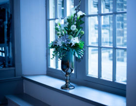 A well-presented vase of flowers on a window sill.