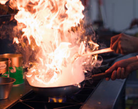 A chef is preparing a curry dish in a large pan with flames.
