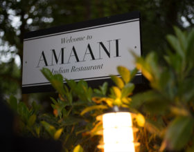 "A sign at the front of the restaurant reads ""Welcome to Amaani""."